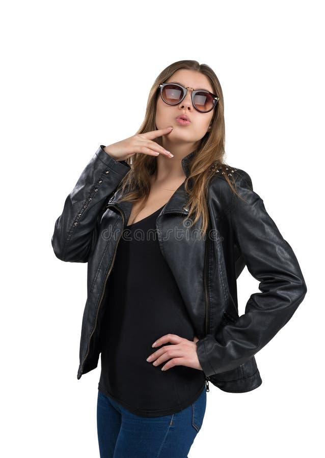 Jovem mulher quente glamoroso em um casaco de cabedal e em uns óculos de sol marrons, isolados no fundo branco Rua, forma da roch fotografia de stock royalty free