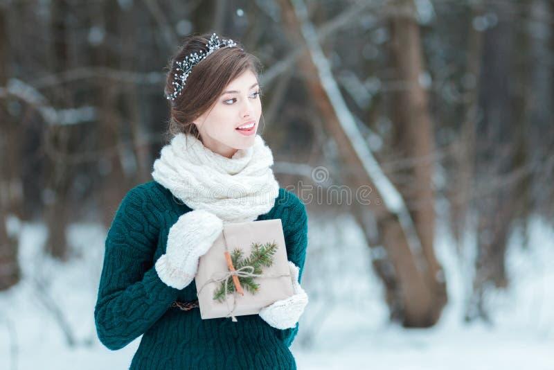 Jovem mulher querendo saber que guarda o presente do Natal foto de stock