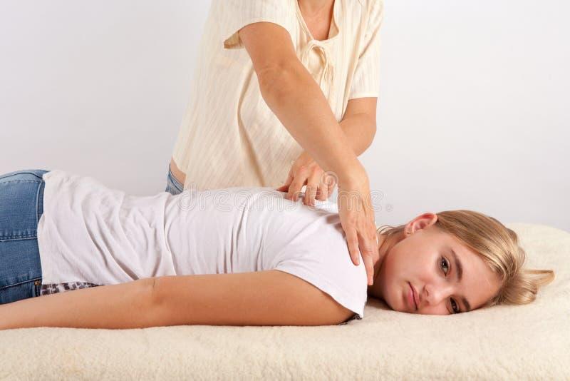 A jovem mulher recebe bowen a terapia imagem de stock