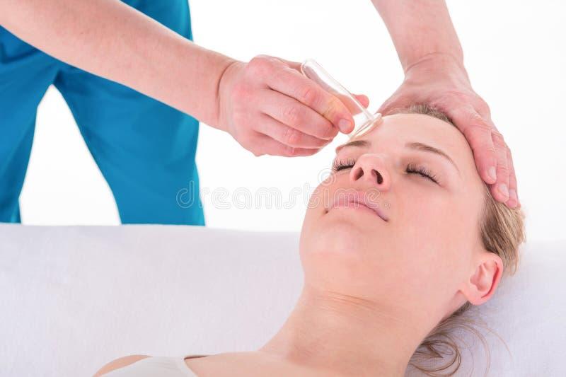 A jovem mulher recebe o tratamento facial colocando facial do rejuvenescimento da massagem em termas do bem-estar da acupuntura foto de stock royalty free