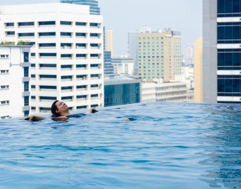 A jovem mulher relaxa na associação no telhado do scyscaper imagem de stock royalty free
