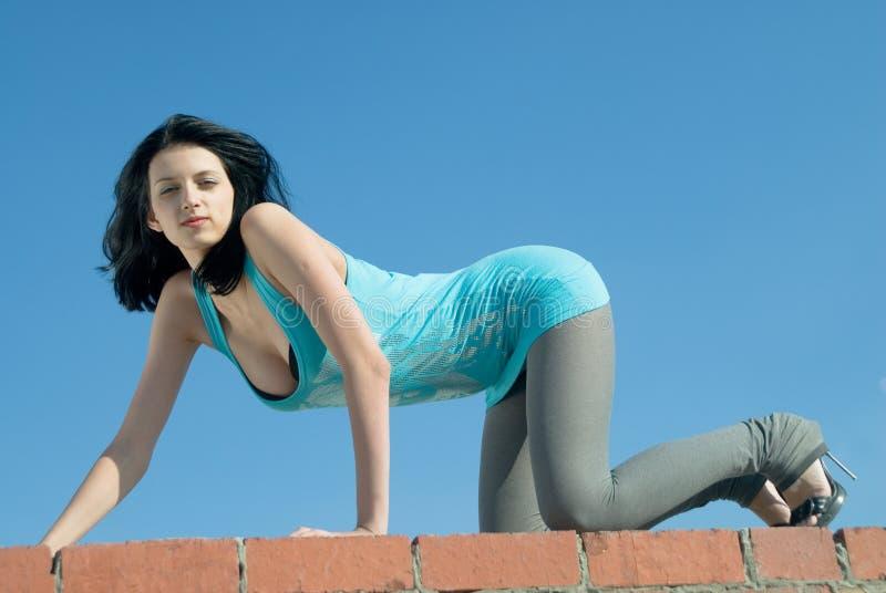 A jovem mulher relaxa no telhado foto de stock