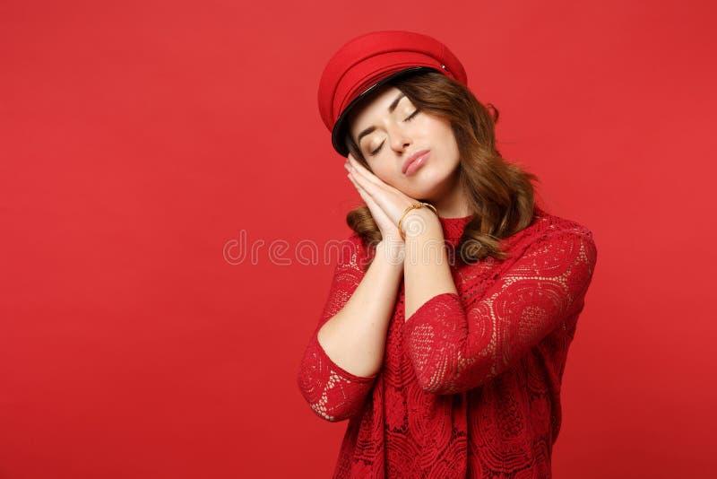 A jovem mulher relaxada no vestido do laço, tampão que mantém os olhos fechou-se, dormindo com mãos perto da cara isolada no verm imagem de stock