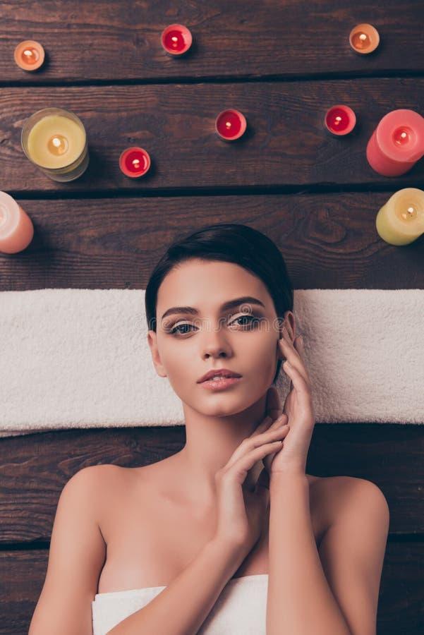 A jovem mulher relaxado bonito que coloca no salão de beleza dos termas no aroma pequeno de toalha e grande colorido candles a ma foto de stock royalty free