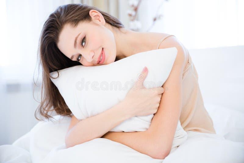 Jovem mulher relaxado feliz que abraça o descanso na cama fotos de stock royalty free