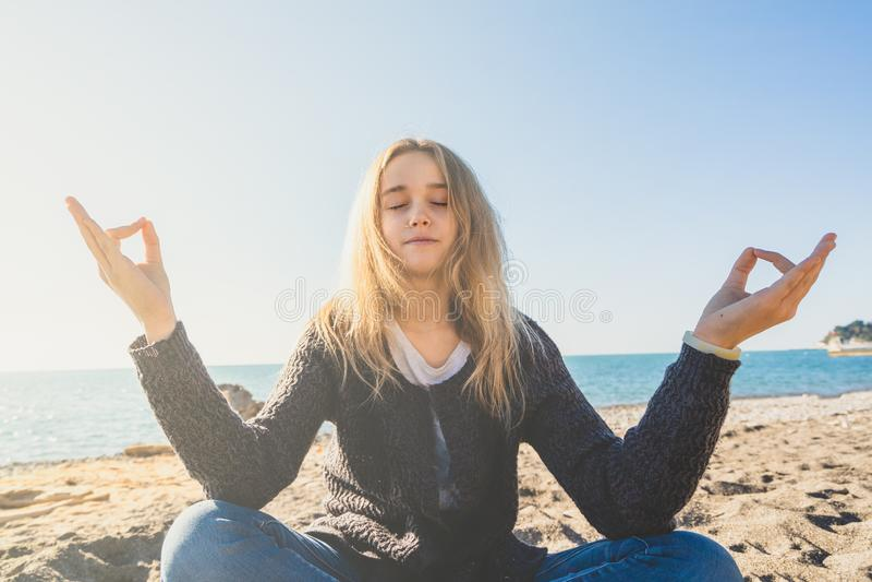 Jovem mulher relaxado feliz que medita em uma pose da ioga na praia fotos de stock royalty free