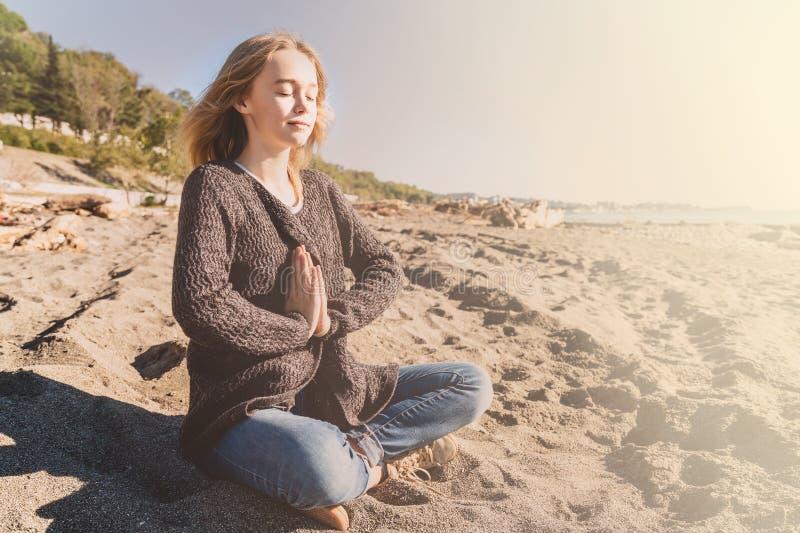 Jovem mulher relaxado feliz que medita em uma pose da ioga na praia imagens de stock royalty free