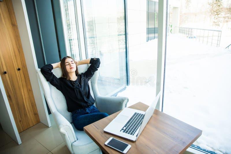 Jovem mulher relaxado feliz que senta-se na tabela com um portátil na frente dela que estica seus braços acima de sua cabeça e qu imagem de stock