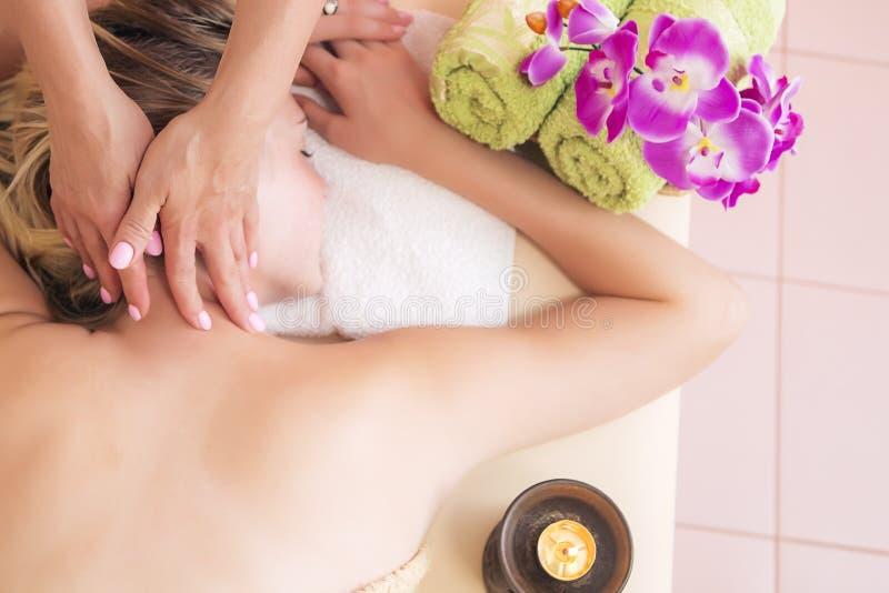 Jovem mulher relaxado na tabela da massagem que recebe o tratamento da beleza em termas do dia imagens de stock