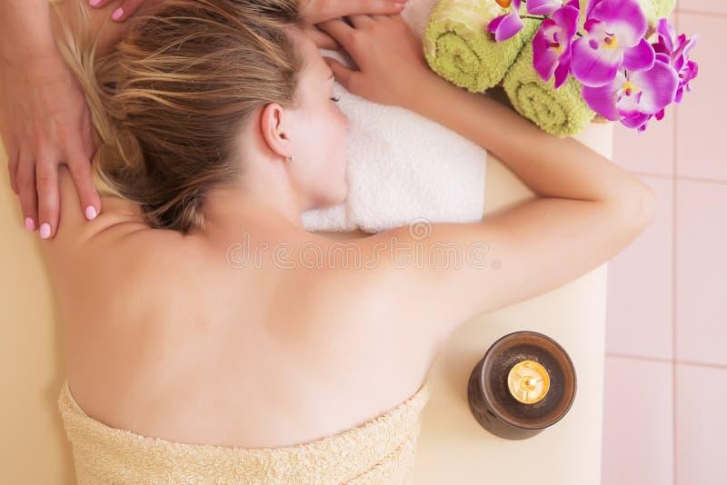Jovem mulher relaxado na tabela da massagem que recebe o tratamento da beleza em termas do dia foto de stock