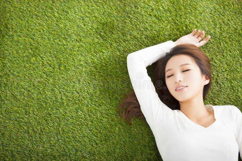 Jovem mulher relaxado que encontra-se na grama fotos de stock royalty free