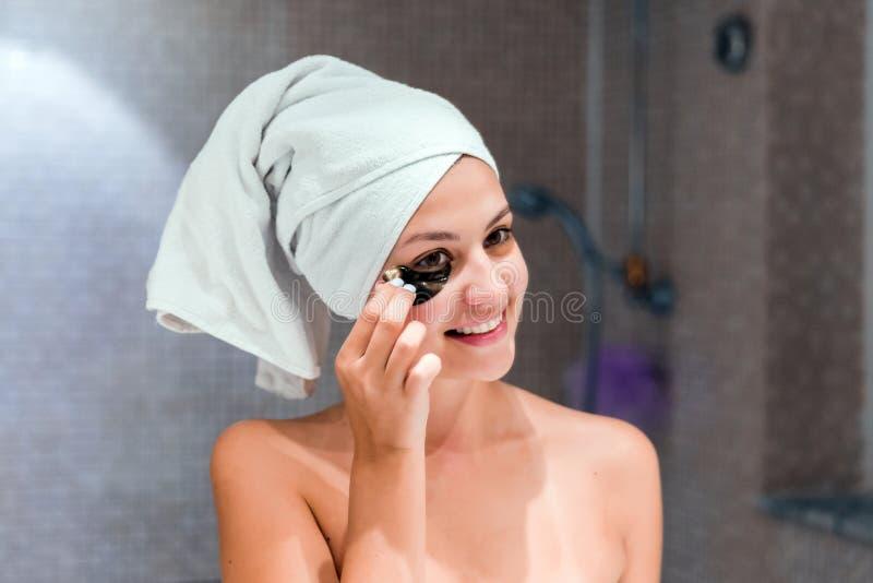 A jovem mulher remove os remendos do sob-olho que olham no espelho em casa no banheiro Skincare da beleza e conceito da manh? do  foto de stock