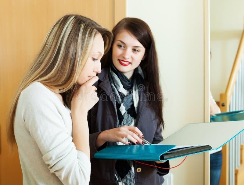 A jovem mulher responde a perguntas do visitante imagens de stock
