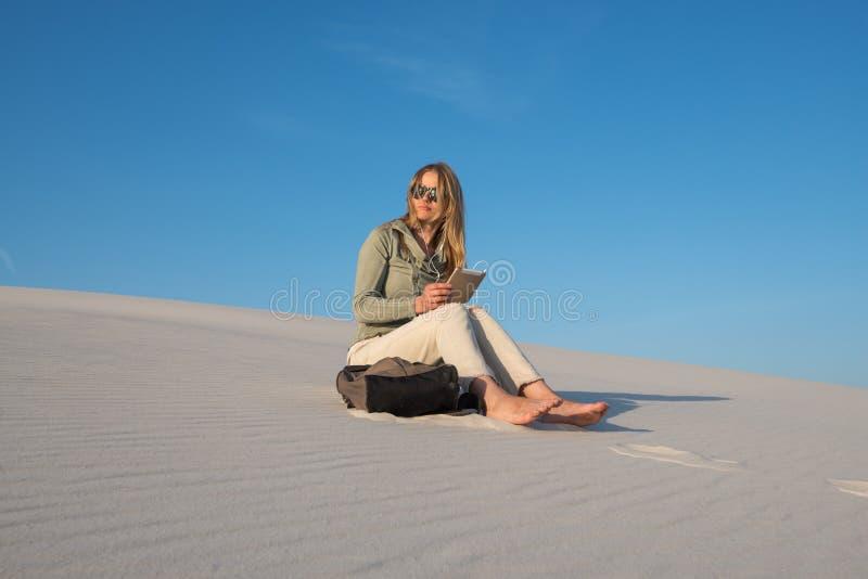 A jovem mulher romântica, louro senta-se com a tabuleta digital no bea fotos de stock