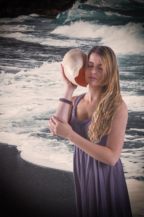 Jovem mulher romance com a concha do mar grande na opinião do mar imagens de stock