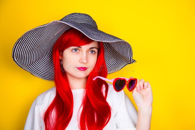 Jovem mulher ruivo atrativa nos óculos de sol e no chapéu no yello fotos de stock
