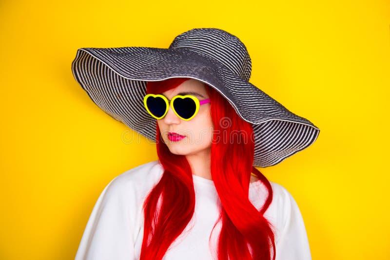 Jovem mulher ruivo atrativa nos óculos de sol e no chapéu no yello fotografia de stock