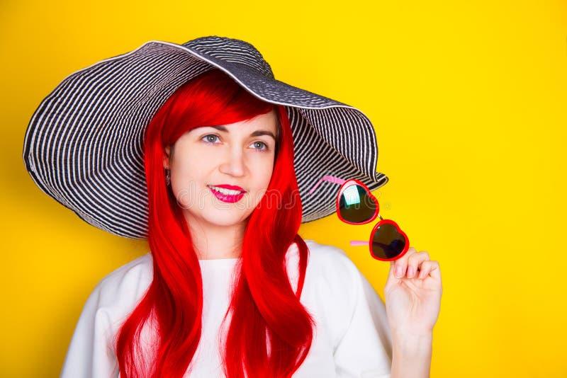 Jovem mulher ruivo atrativa nos óculos de sol e no chapéu no yello imagem de stock