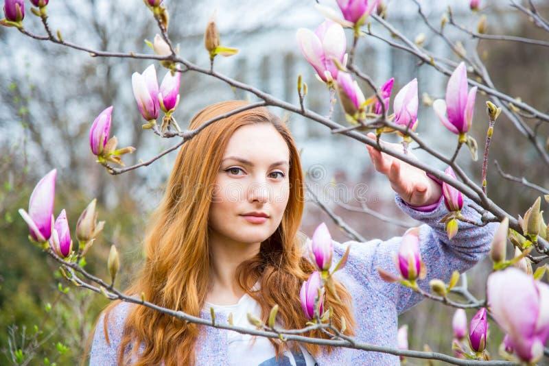 Jovem mulher ruivo bonita que está perto da magnólia de florescência imagem de stock