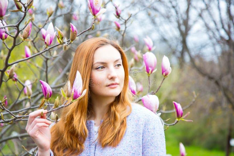 Jovem mulher ruivo bonita que está perto da magnólia de florescência imagem de stock royalty free