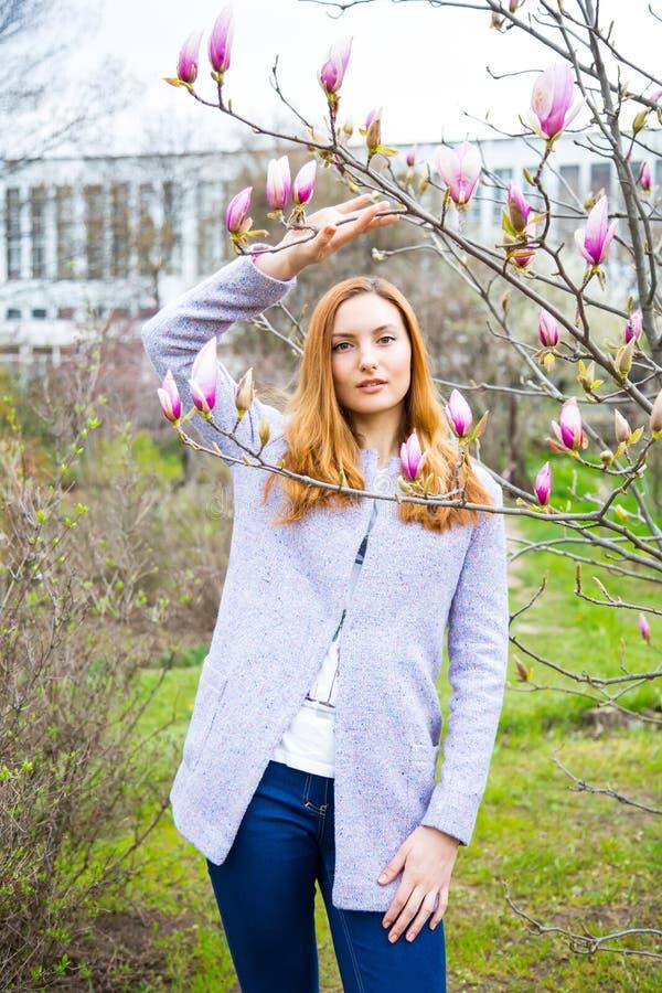 Jovem mulher ruivo bonita que está perto da magnólia de florescência foto de stock