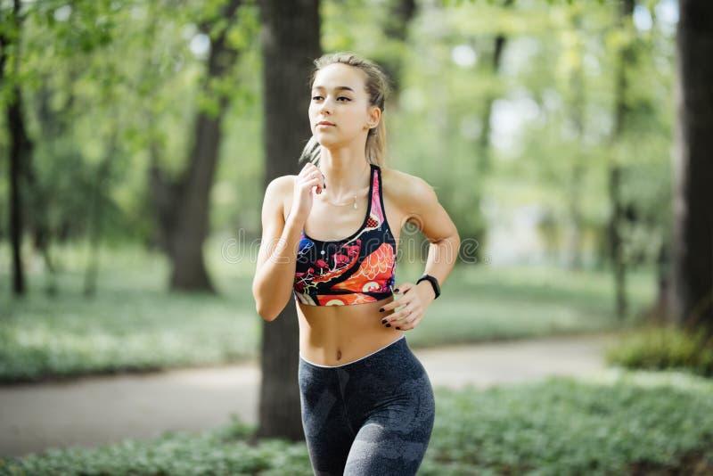 Jovem mulher running do retrato Corredor fêmea que movimenta-se durante o exercício exterior no parque no dia de verão da mola Me foto de stock