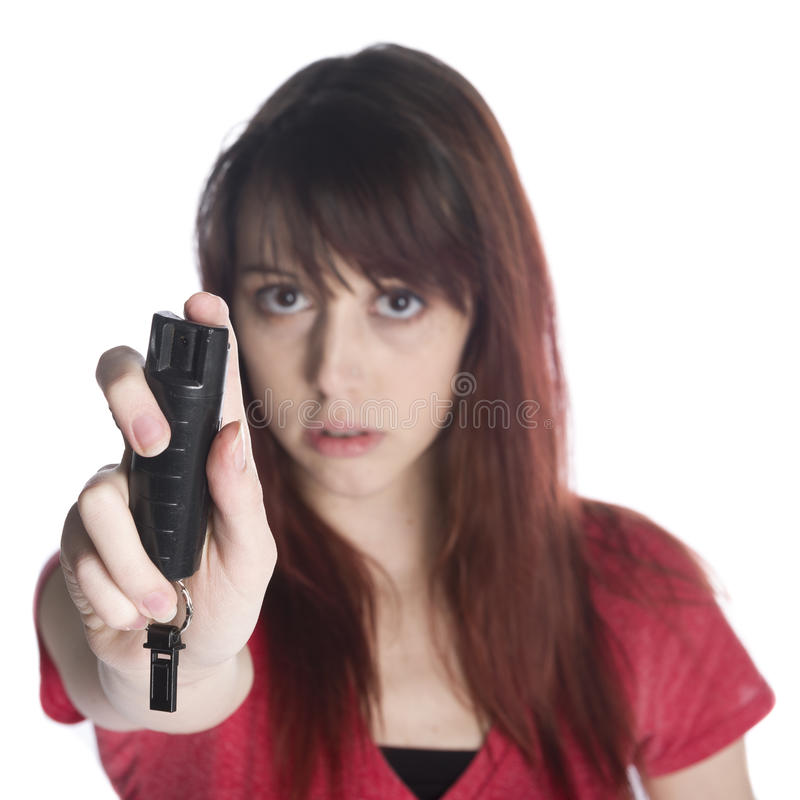 Jovem mulher séria que guarda o pulverizador preto do gás lacrimogêneo imagens de stock