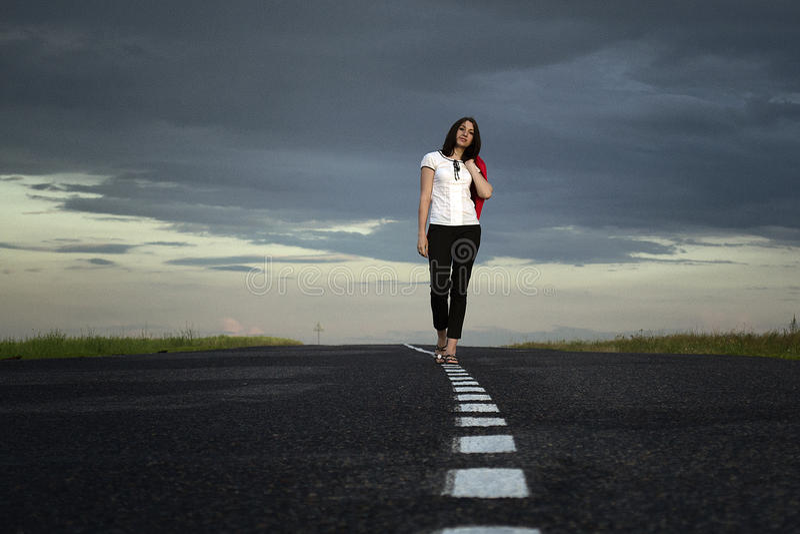 Jovem mulher só que anda no meio da estrada imagem de stock