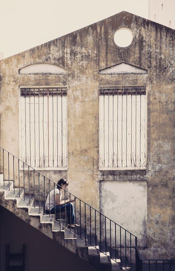 Jovem mulher só que senta-se nas etapas das escadas velhas que guardam um telefone celular fotos de stock royalty free