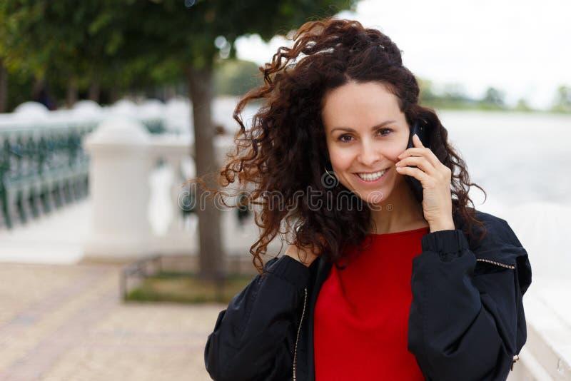 Jovem mulher 30s de sorriso fora da fala no telefone celular, olhando a câmera, estadas no vento, fundo borrado fotografia de stock royalty free