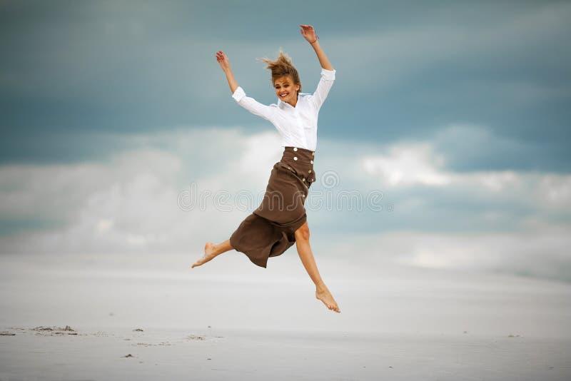 A jovem mulher salta na areia no deserto e em risos alegres imagem de stock