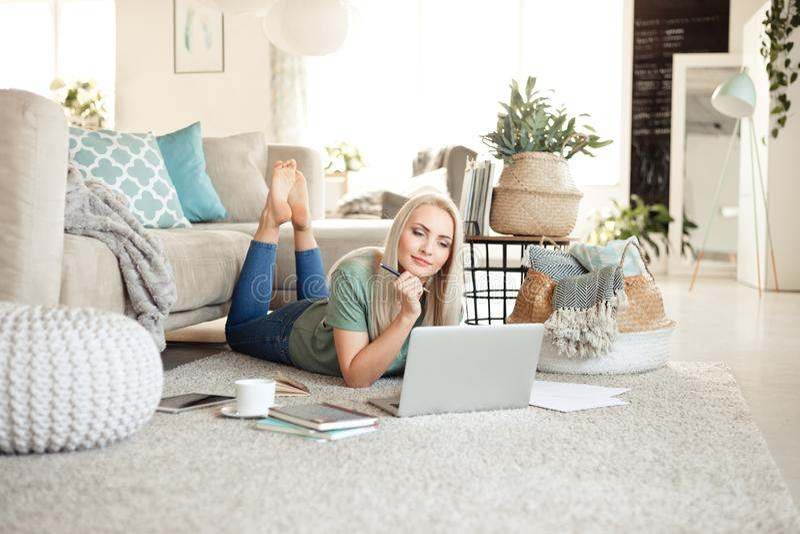 Jovem mulher satisfeito que usa um portátil na sala de visitas fotos de stock royalty free