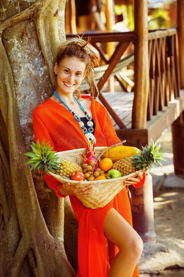 A jovem mulher saudável bonita está guardando a cesta do frui tropical fotos de stock royalty free