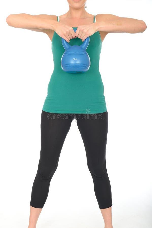 Jovem mulher saudável do ajuste que levanta um peso de Bell da chaleira 5kg foto de stock