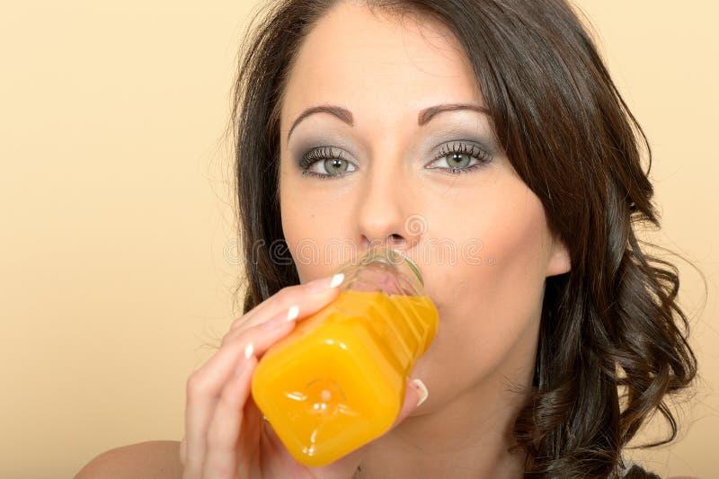 Jovem mulher saudável que bebe uma garrafa do suco de laranja fresco imagens de stock