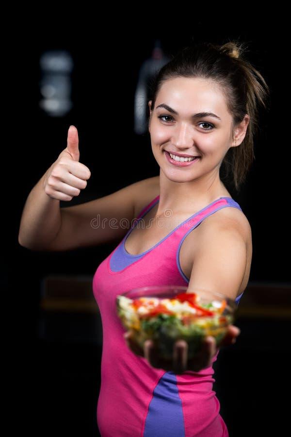 Jovem mulher saudável que come a salada verde dos vegetais no gym escuro foto de stock