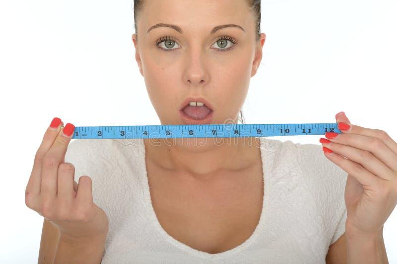 Jovem mulher saudável que mantém uma fita métrica chocada imagem de stock