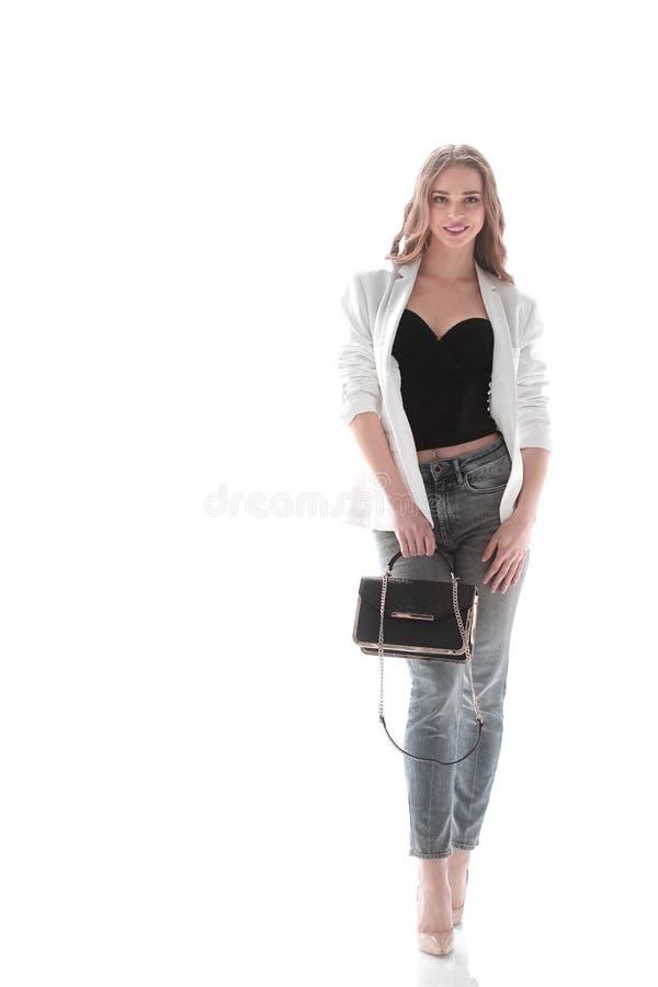 A jovem mulher segura com um saco gracioso vai para a frente Isolado no branco Foto com espa?o da c?pia imagem de stock royalty free