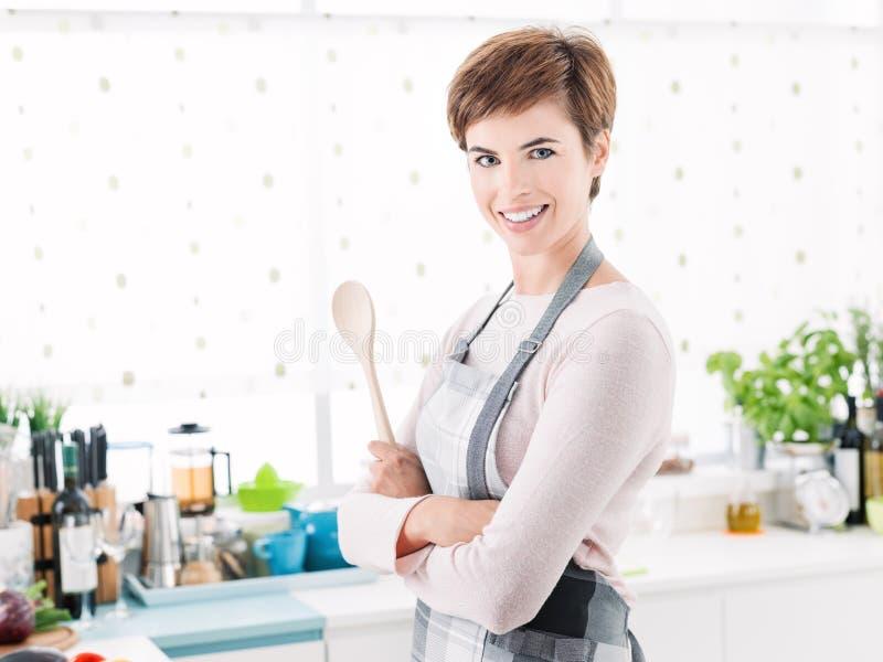Jovem mulher segura de sorriso com o avental que levanta no kitche foto de stock royalty free