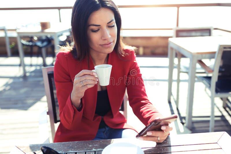 A jovem mulher segura que bebe o quando do latte do chá verde de Matcha que texting com seu telefone celular em wodden a tabela n foto de stock royalty free