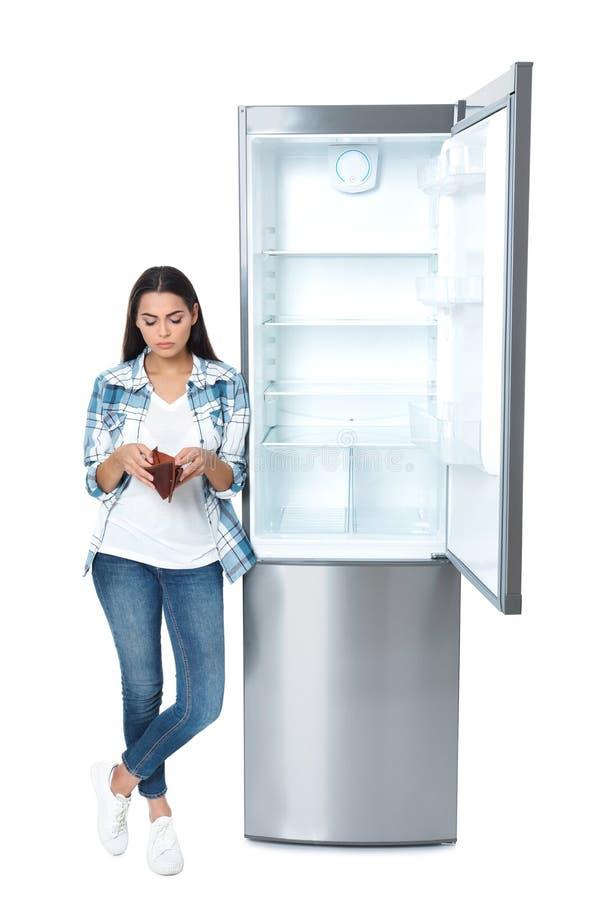 Jovem mulher sem o dinheiro na carteira perto do refrigerador vazio fotografia de stock
