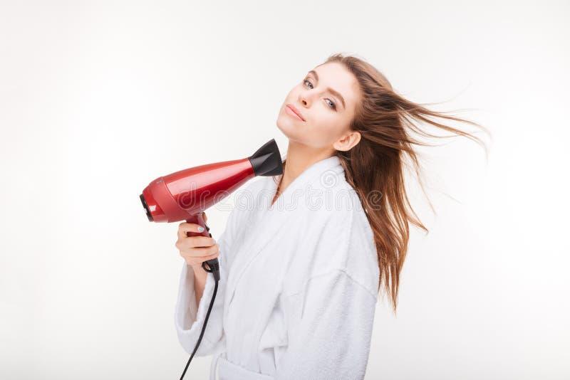 Jovem mulher sensual bonita em cabelo de secagem do roupão com secador foto de stock