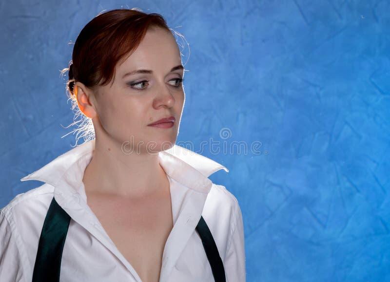 Jovem mulher sensual bonita na camisa do ` s dos homens e laço em um fundo azul imagem de stock royalty free