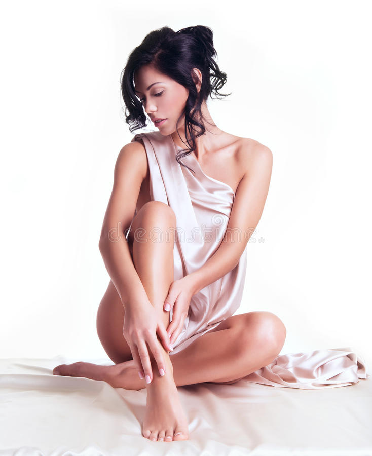 Jovem mulher sensual com corpo bonito na seda bege fotografia de stock royalty free