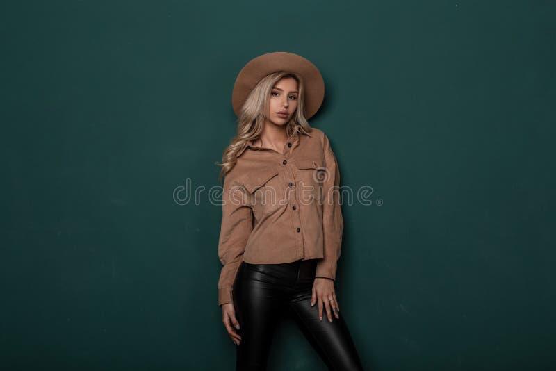 Jovem mulher sensual maravilhosa em calças de couro pretas no estilo retro em um chapéu elegante bege em um levantamento bege da  foto de stock royalty free