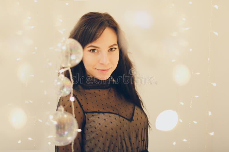 Jovem mulher sensual no vestido de cocktail que fica de sorriso sobre o fundo das luzes imagens de stock royalty free