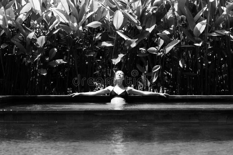 Jovem mulher sensual que relaxa na piscina exterior da infinidade dos termas cercada com hortaliças tropicais luxúrias de Ubud, B foto de stock royalty free