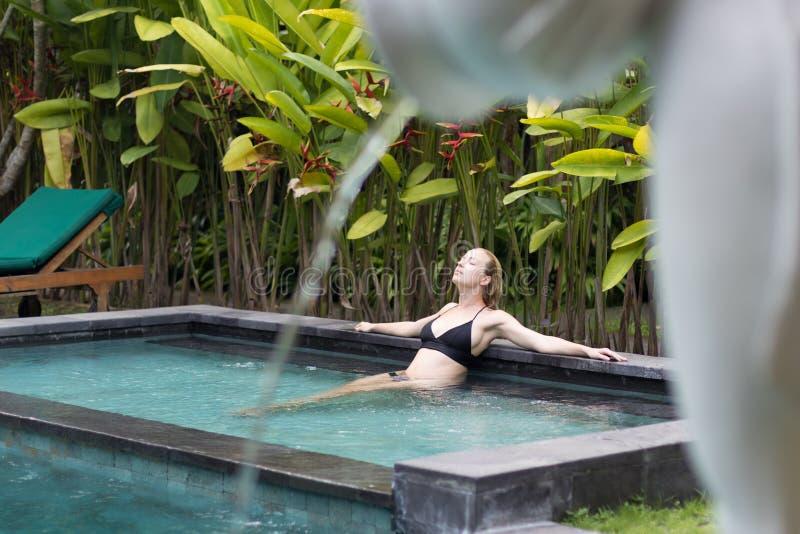 Jovem mulher sensual que relaxa na piscina exterior da infinidade dos termas cercada com hortali?as tropicais lux?rias de Ubud, B foto de stock
