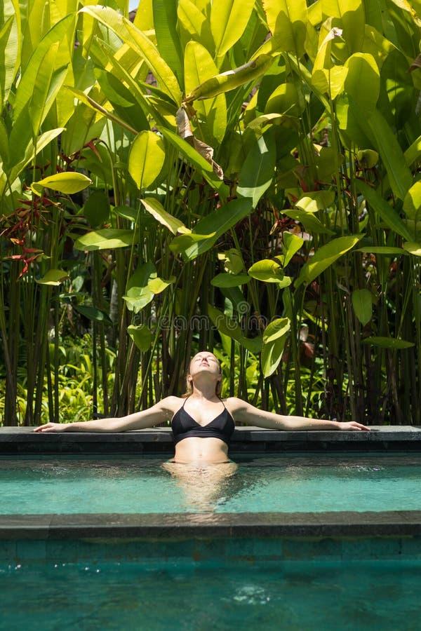 Jovem mulher sensual que relaxa na piscina exterior da infinidade dos termas cercada com hortali?as tropicais lux?rias de Ubud, B imagem de stock royalty free
