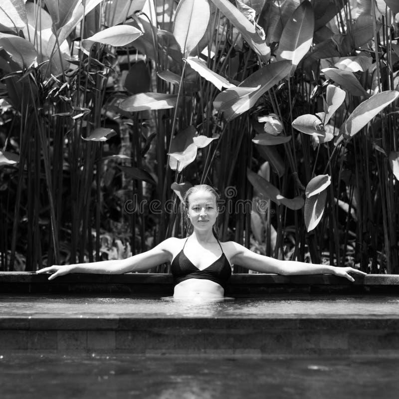 Jovem mulher sensual que relaxa na piscina exterior da infinidade dos termas cercada com hortali?as tropicais lux?rias de Ubud, B fotos de stock royalty free